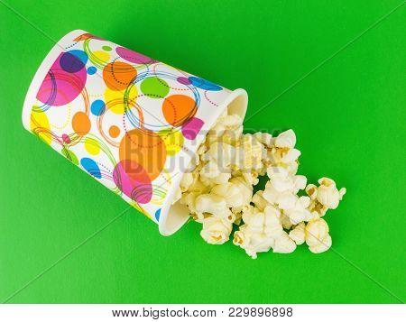 Popcorn Is Poured From A Multi-colored Paper Cup On A Green Table. Vegetarian Food From Corn.