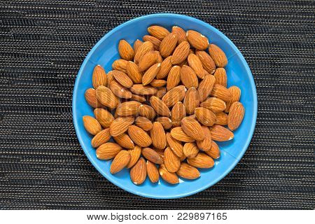 Almond In Blue Plate On Dark Background. Brown Almond For Food. Organic Food Banner Template. Tasty