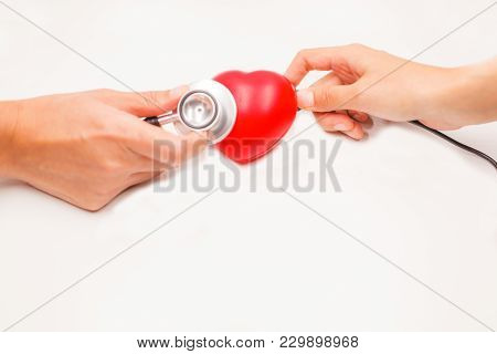 Hands With Stethoscope And Charging Cable To Check And Cure Heart On White Background. Heart Disease