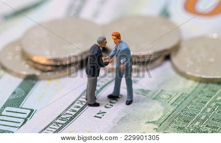 Businessmen Toy Shaking Hands On Cash. Tiny Businessmen Figurines On Money Background. Finance Deal