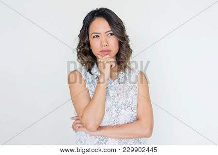 Portrait Of Pensive Asian Woman Leaning Chin On Hand And Looking Aside. Young Lady Thinking Over Imp
