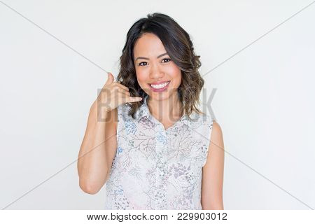 Joyful Asian Woman Imitating Phoning. Smiling Young Lady Showing Call Me Gesture With Raised Hand At