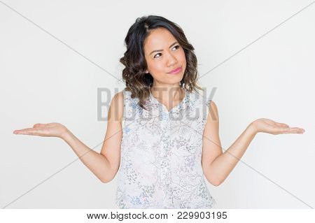 Pensive Asian Woman Spreading Hands. Young Lady Presenting Something With Both Hands Or Illustrating