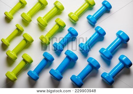 Many Blue And Green Dumbbells On A White Background ,concept Preparing To Fitness Sports Equipment T