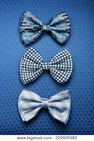 Three Bow-ties Against Blue Textile Background