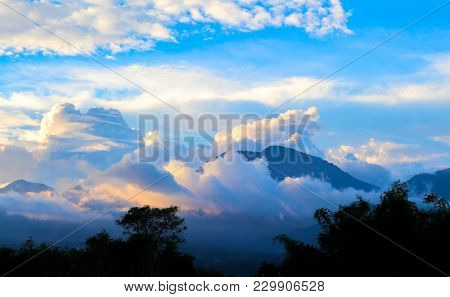 Spectacular Sunset In Mountains. Tropical Golden Hour Landscape. White Fluffy Cloud Around Mountain.