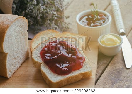 Delicious Toast Bread Served With Butter And Spread With Strawberry Jam On Wood Cutting Board Put On