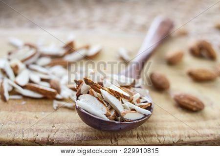 Whole And Chopped Almond Nuts On A Wooden Board And In A Wooden Oak Spoon On A Rattan Table.