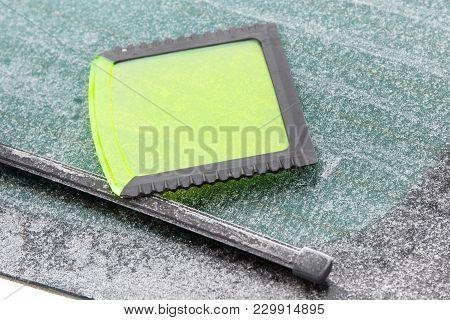 Green Ice Scraper Lying On Window Of Car, Winter Problems In Transportation
