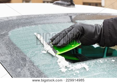 Hand Of Man In Leather Glove Scraping Ice Or Snow From Window Of Car