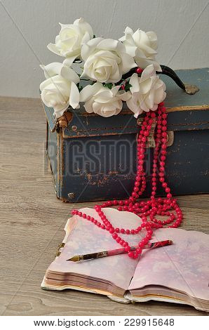 An Old Worn Out Blue Suitcase With A Bunch Of Artificial White Roses, A String Pink Beads, A Note Bo