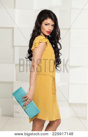 Beautiful Brunette Woman With Blue Clutch Handbag