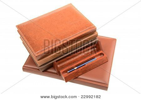 Pile Of Organizers And Pen In  Wooden Case Isolated