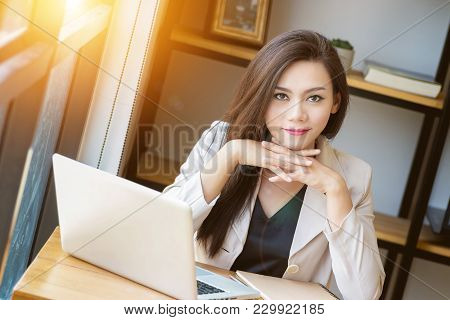 Portrait Of Beautiful And Confident Asian Business Woman In Working Age Using Computer Laptop Techno