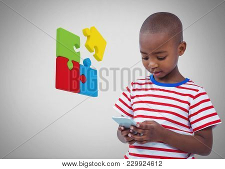 Digital composite of Boy against grey background with phone device and jigsaw puzzle pieces