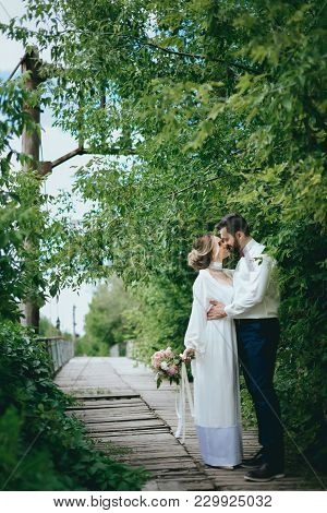 The Bride And Groom Posing On A Suspension Bridge