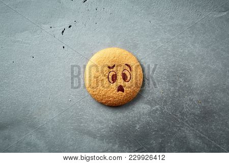Round Cookie With Sad Emotion, Face With Emotion On A Dark Concrete Backdrop