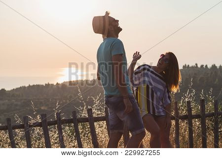 Young Couple In Love Enjoying Sunset Over The Sea
