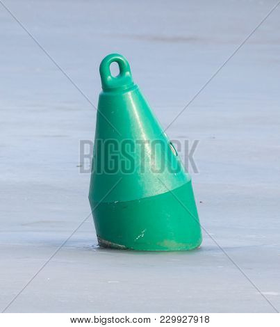 Green Buoy In A Large Pond