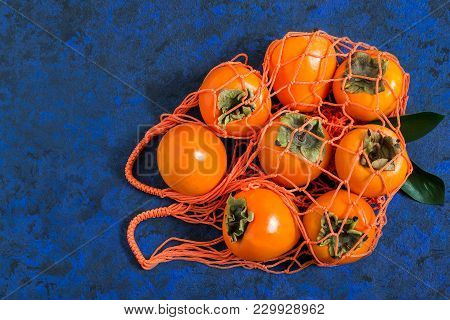 Ripe Persimmon In Orange String Bag On Blue Textured Background. Persimmon Is Source Of Vitamin C, I