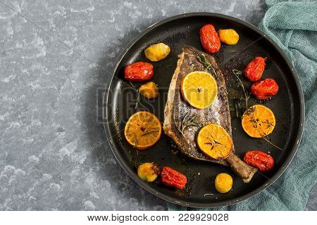Flounder In Pan Baked With Mandarins And Cherry Tomatoes. Pan On Gray Background With Gauze Napkin