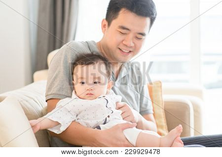 Asian family at home. Father babysitting son, living lifestyle indoors.