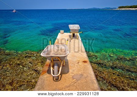 Wheelbarrow On Small Island Dock Waiting For Goods Delivery, Mediterranean Archipelago