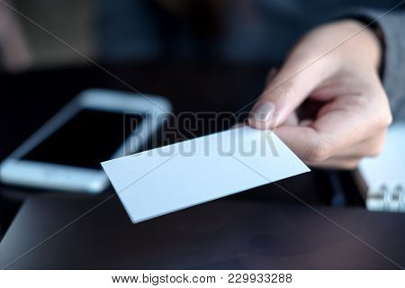 Business Woman Holding And Giving  Business Card To Someone With Mobile Phone And Notebook On Table