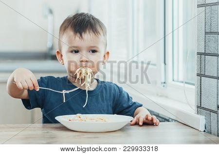 The Child In The Kitchen At The Table Eating Macaroni And Interesting View From The Top