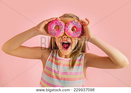 Young Beautiful Happy And Excited Blond Girl 8 Or 9 Years Old Holding Two Donuts On Her Eyes Looking