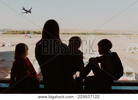 Family Plane Travel- Mother With Kids Looking At Planes In Airport