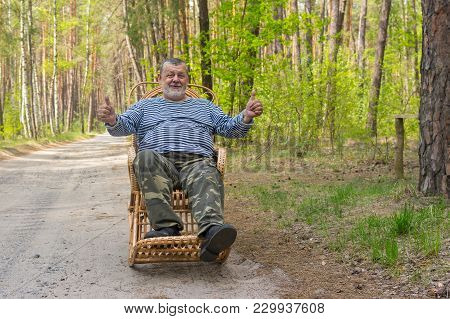 Smiling Senior Man Sitting In A Wicker Rocking-chair In Spring Forest.