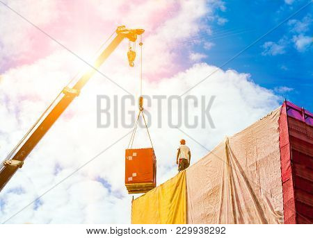 Mobile Crane On A Background Of Sky. Load On The Hook Of The Crane. A Man Builder In A Helmet Takes
