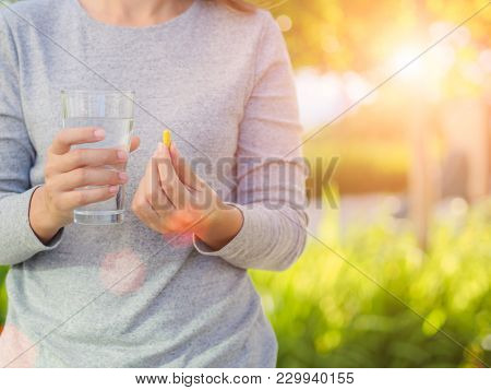 Close Up Of Woman Taking In Pill With Bokeh Background. Health Care And Medical Concept.