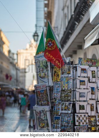 Lisbon, Portugal - July 2016: Post-cards And National Flag Inside Exhibitor And Rua Augusta Arch In