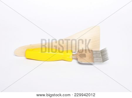 Colorful And Crisp Image Of Uncapping Fork And Honey Scraper On White