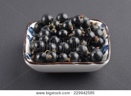 Colorful And Crisp Image Of Blackcurrant In Bowl On Black Background