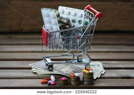 Pharmaceutical Drugs In A Shopping Cart Above Money, Suggesting Increase Of Health Expenses