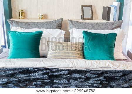 An Interior Picture Of A Bed With Many Pillow And A Black Velvet Blanket And Luxury Candle And Frame