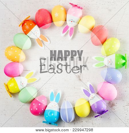 Easter Scene With Colored Eggs And Bunnies With Happy Easer Greetings
