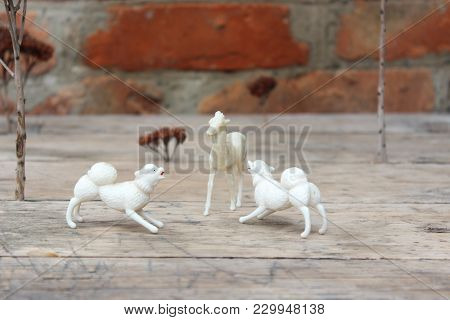 Figurine Of Deer And Dog On Brick Wall Background