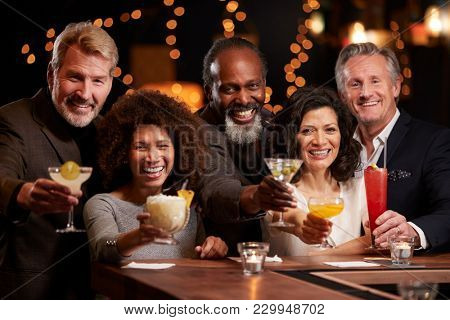 Portrait Of Middle Aged Friends Celebrating In Bar Together