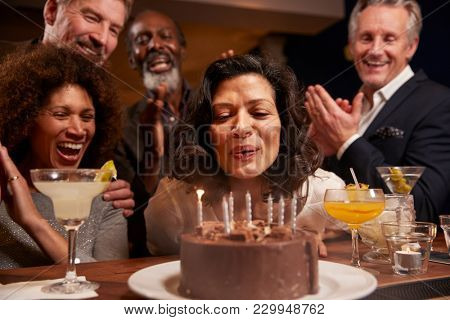 Group Of Middle Aged Friends Celebrating Birthday In Bar