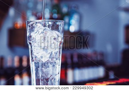 cubes of ice in glass on bar. cocktail