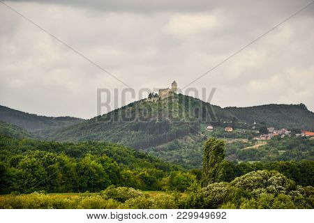 Aerial View Of Podhradie Castle And Village In Slovakia. Castle On Hill With Tower Surrounded By Vil