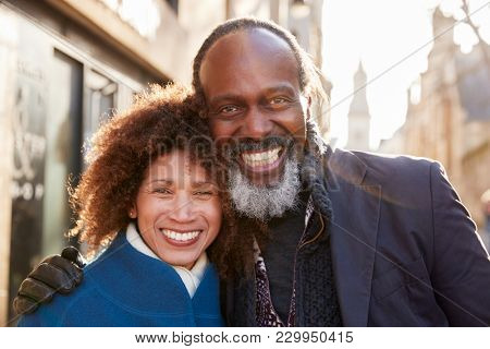 Portrait Of Mature Couple Walking Through City In Fall Together