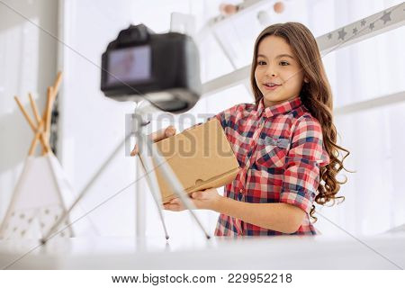 Introductory Remarks. Pleasant Cheerful Pre-teen Girl In A Checked Shirt Holding A Box In Her Hands
