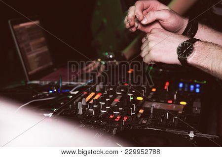 DJ mixes tracks at a party. DJ control panel