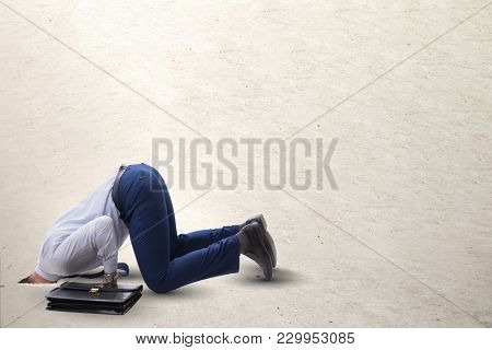 Businessman hiding his head in sand escaping from problems