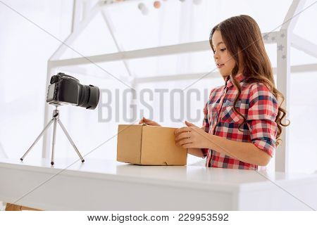 No More Waiting. Sweet Pre-teen Girl Being About To Open A Box Standing On The Table In Front Of Her